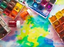 Aquarellfarben, -bürsten und -PALETTE auf dem bunten Hintergrund Stockfotos