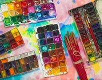 Aquarellfarben, -bürsten und -PALETTE auf dem bunten Hintergrund Stockfotografie