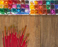 Aquarellfarben, -bürsten und -PALETTE auf einem hölzernen Hintergrund Lizenzfreie Stockfotos