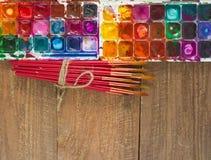 Aquarellfarben, -bürsten und -PALETTE auf einem hölzernen Hintergrund Lizenzfreies Stockfoto