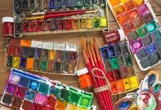 Aquarellfarben, -bürsten und -PALETTE auf einem hölzernen Hintergrund Lizenzfreie Stockbilder