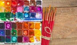 Aquarellfarben, -bürsten und -PALETTE auf einem hölzernen Hintergrund Stockbilder