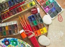 Aquarellfarben, -bürsten und -PALETTE auf hölzernem Hintergrund Lizenzfreie Stockbilder