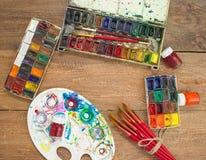 Aquarellfarben, -bürsten und -PALETTE auf hölzernem Hintergrund Stockbild