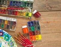 Aquarellfarben, -bürsten und -PALETTE auf hölzernem Hintergrund Lizenzfreie Stockfotos