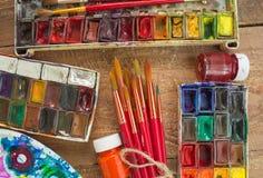 Aquarellfarben, -bürsten und -PALETTE auf hölzernem Hintergrund Lizenzfreie Stockfotografie