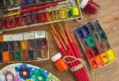 Aquarellfarben, -bürsten und -PALETTE auf hölzernem Hintergrund Stockfotos