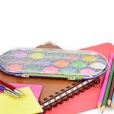 Aquarellfarben, Notizbücher und anderer Schulbedarf lokalisiert auf weißem Hintergrund Freier Platz für Text stockfotos