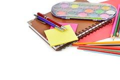 Aquarellfarben, Notizbücher und anderer Schulbedarf lokalisiert auf weißem Hintergrund Freier Platz für Text lizenzfreie stockfotografie