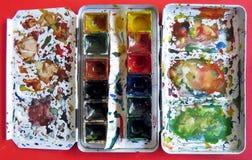 Aquarellfarbenkasten auf roter Tabelle Stockbilder