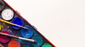 Aquarellfarbenpalette mit zwei Pinseln, die auf sie mit einem weißen Hintergrund legen Lizenzfreie Stockbilder