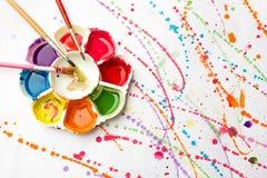 Aquarellfarbwanne mit Bürste auf Malereihintergrund Lizenzfreies Stockfoto