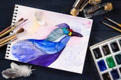 Aquarellmalerei des blauen Vogels und der künstlerischen Werkzeuge auf Tabelle Stockfotos