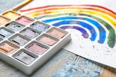 Aquarellmalerei des Regenbogens auf hölzernem Hintergrund Stockfotografie