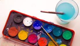 Aquarellmalereipalette mit Glas Farbenwasser nahe bei ihm Stockfotografie