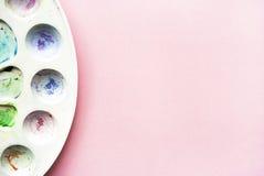 Aquarellpalette auf einem rosa Hintergrund mit dem Platz für Ihren Text Flache Lage Lizenzfreie Stockbilder