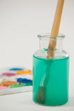 Aquarellpalette und -Pinsel mit blauer Farbe tauchten in Wasser ein Stockfotos