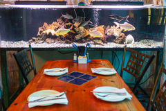 Aquarium close to a table inside a restaurant Royalty Free Stock Photo
