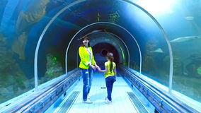 Aquarium in Hurghada, Egypt. Underwater tunnels, a fascinating underwater world and modern technology. A young brunette woman in a yellow jacket and jeans stock video