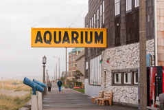 An aquarium sign over a long walkway along the beach in Oregon. Royalty Free Stock Photos