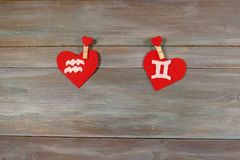 Aquarius and twins. signs of the zodiac and heart. wooden backgr royalty free stock photo