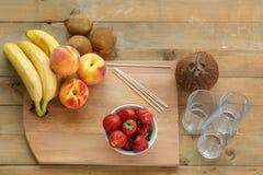 Aquartele para o cocktail de fruto em morangos de uma placa de corte, bananas, pêssegos Imagem de Stock