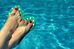 Aquatic Relaxing. Background is filled with aqua water. Woman has on polka dotted flip flops and has red painted toe nails. Feet only stock image