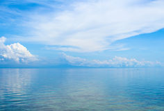 Aquatic seascape with distant island and blue sky. Relaxing sea view with still seawater. Stock Photo