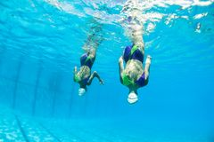 Aquatic Synchronized Girls Pairs Underwater. Aquatic synchronized unidentified girls swimmers dance pairs moves closeup underwater photo action Royalty Free Stock Photography