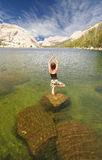 Aquatic Yoga. A fit woman stands in a yoga pose named The Tree on a rock in a lake in Yosemite national park Stock Images
