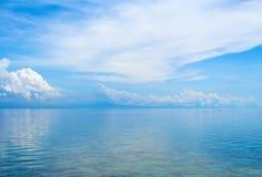 Aquatisch zeegezicht met ver eiland en blauwe hemel Ontspannende overzeese mening met nog zeewater stock foto