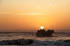 Aqueça a imagem tonificada de um por do sol com uma destruição do navio e um rebanho dos pássaros de mar mostrados em silhueta co foto de stock