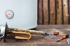Aquecedor de água quebrado com elementos de aquecimento, no fundo de madeira foto de stock