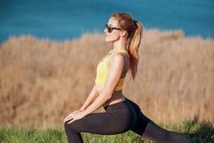 Aquecer-se antes de movimentar-se Retrato do close-up da jovem mulher bonita na roupa dos esportes que faz esticando exercícios e Imagem de Stock