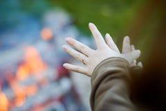 Aqueceu suas mãos em um fogo Imagens de Stock Royalty Free
