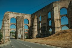 Aqueduct with arches and rectangular pillars on the road to Elvas. Architectural structure of the Amoreira Aqueduct with arches and rectangular pillars on the stock photo