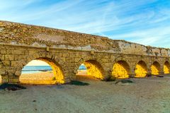 The aqueduct on sunset. The aqueduct, built in the early Byzantine period. Fantastic sunset on the Mediterranean coast in Caesarea. The sandy beach is trampled Stock Photos