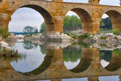Aqueduct and its reflection. The well-known antique bridge-aqueduct Pont du Gard in Provence royalty free stock photography