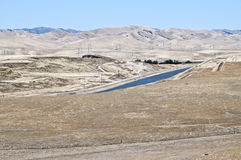 Aqueduct,  Northern California. The California Aqueduct flows through the burned out grasses of fields of the central portion of Northern California, parched by Royalty Free Stock Photography