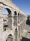 Aqueduct of Segovia. View of town through arch of aqueduct Stock Photos