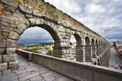 The aqueduct and Segovia in May day. The well-known antique aqueduct and ancient Segovia in cloudy May day royalty free stock photography