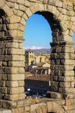 Aqueduct of Segovia, Spain. Church of the Saints Justus and Pastor seen through an arch of the Aqueduct of Segovia, Spain. Vertical view with blue sky on the Stock Image