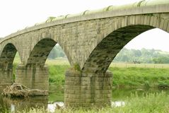 Aqueduct. A stone built aqueduct over the river Ribble in Lancashire UK with a tractor hay turning framed by the arch Stock Images