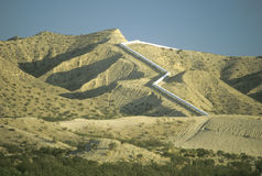 An aqueduct which supplies water to Los Angele. S winding down a hill in the California desert Stock Photography