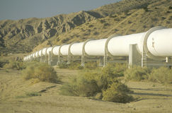 An aqueduct which supplies water to Los Angeles. Winding down a hill in the California desert Stock Photos