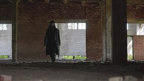 Aquela é uma construção abandonada quebrada do quadro agradável A sala é um homem em uma capa de chuva e em um chapéu filme