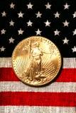 Aquila americana dell'oro sulla bandiera americana Fotografia Stock