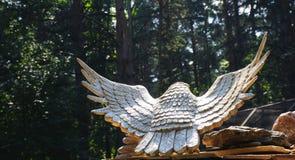 Aquila di legno scolpita in foresta Immagine Stock