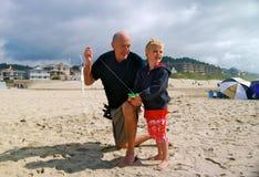 Aquilone della mosca del bambino e del nonno alla spiaggia Immagine Stock