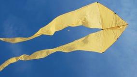 Aquilone giallo con due code che si librano nel cielo blu e nel giorno soleggiato stock footage